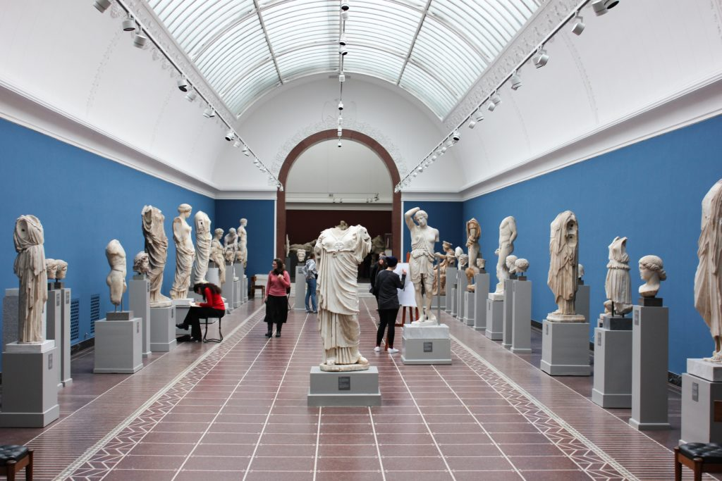 Visitors looking at marble statues in a museum.